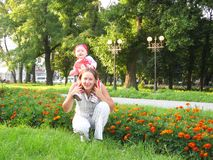 Happy mum and the daughter in park with flowers Royalty Free Stock Photo