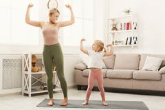 Happy mother and daughter having training at home. Young mother showing her little daughter exercises. Happy girls training at home. Motherhood and sporty Royalty Free Stock Photo