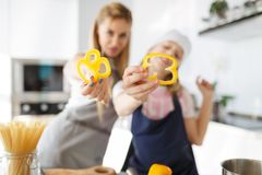 Happy mother and daughter hold pepper slices in the kitchen room. The process of cooking a healthy dish from vegetables. stock photo