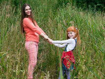 Happy mother and daughter holding hands and looking into the frame Stock Photography