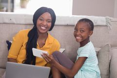 Happy mother and daughter holding laptop and mobile phone at home Royalty Free Stock Photography