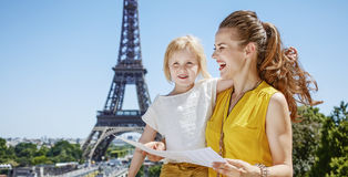 Happy mother and daughter holding map against Eiffel tower Royalty Free Stock Images