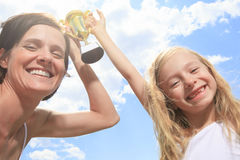 Happy mother and daughter holding a trophy high up Stock Photos