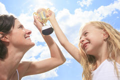 Happy mother and daughter holding a trophy high up Royalty Free Stock Photos