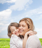 Happy mother and daughter hugging. Family, child and happiness concept - hugging mother and daughter Royalty Free Stock Photo