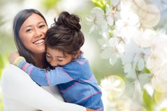 Happy mother and daughter hugging. Family, motherhood and people concept - happy mother and daughter hugging over cherry blossom background stock images