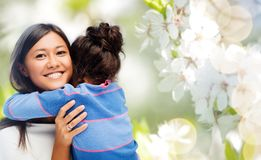 Happy mother and daughter hugging. Family, motherhood and people concept - happy mother and daughter hugging over cherry blossom background stock photography