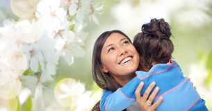 Happy mother and daughter hugging. Family, motherhood and people concept - happy mother and daughter hugging over cherry blossom background royalty free stock photo