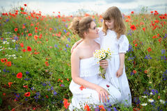 Happy mother and daughter hugging among the flowering meadows of Royalty Free Stock Image