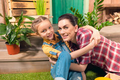 Happy mother and daughter hugging on green lawn Royalty Free Stock Image