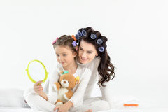 Happy mother and daughter hugging while holding hand mirror and teddy bear Stock Image