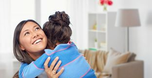 Happy mother and daughter hugging at home. Family, motherhood and people concept - happy mother and daughter hugging over over home room background stock image