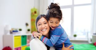 Happy mother and daughter hugging at home. Family, motherhood and people concept - happy mother and daughter hugging over over kids room at home background stock photography