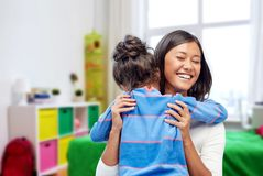 Happy mother and daughter hugging at home. Family, motherhood and people concept - happy mother and daughter hugging over over kids room at home background stock photo