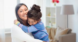Happy mother and daughter hugging at home. Family, motherhood and people concept - happy mother and daughter hugging over over home room background royalty free stock photography