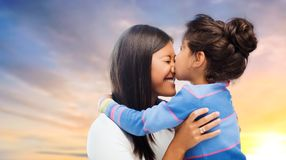 Happy mother and daughter hugging and kissing. Family, motherhood and people concept - happy mother and daughter hugging and kissing over evening sky background royalty free stock image