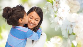 Happy mother and daughter hugging and kissing. Family, motherhood and people concept - happy mother and daughter hugging and kissing over cherry blossom royalty free stock photos