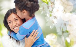 Happy mother and daughter hugging and kissing. Family, motherhood and people concept - happy mother and daughter hugging and kissing over cherry blossom royalty free stock image
