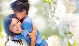 Happy mother and daughter hugging and kissing. Family, motherhood and people concept - happy mother and daughter hugging and kissing over cherry blossom royalty free stock images