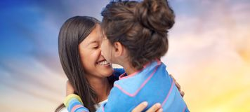 Happy mother and daughter hugging and kissing. Family, motherhood and people concept - happy mother and daughter hugging and kissing over evening sky background royalty free stock images