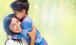 Happy mother and daughter hugging and kissing. Family, motherhood and people concept - happy mother and daughter hugging and kissing over green holidays lights royalty free stock photo