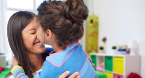 Happy mother and daughter hugging and kissing. Family, motherhood and people concept - happy mother and daughter hugging and kissing over kids room at home stock images
