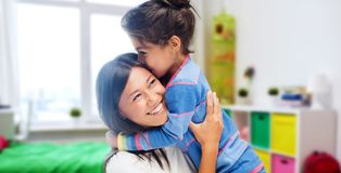 Happy mother and daughter hugging and kissing. Family, motherhood and people concept - happy mother and daughter hugging and kissing over kids room at home royalty free stock photo