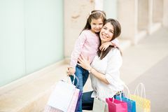 Mother and daughter hugging after shopping spree at mall. Happy mother and daughter hugging outside a mall with lots of shopping bags Royalty Free Stock Photos