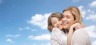 Happy mother and daughter hugging over blue sky Royalty Free Stock Photo