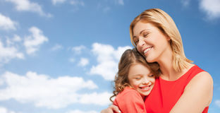 Happy mother and daughter hugging over blue sky Royalty Free Stock Photography