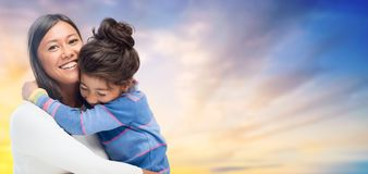 Happy mother and daughter hugging over evening sky. Family, motherhood and people concept - happy mother and daughter hugging over evening sky background stock photos