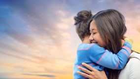 Happy mother and daughter hugging over evening sky. Family, motherhood and people concept - happy mother and daughter hugging over evening sky background royalty free stock photo