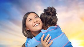 Happy mother and daughter hugging over evening sky. Family, motherhood and people concept - happy mother and daughter hugging over evening sky background stock image