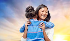 Happy mother and daughter hugging over evening sky. Family, motherhood and people concept - happy mother and daughter hugging over evening sky background royalty free stock photography
