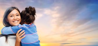 Happy mother and daughter hugging over evening sky. Family, motherhood and people concept - happy mother and daughter hugging over evening sky background royalty free stock photos