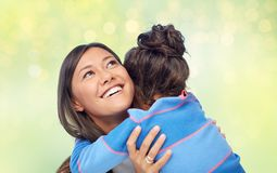 Happy mother and daughter hugging over green Stock Photography