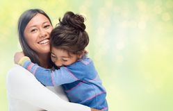 Happy mother and daughter hugging over green. Family, motherhood and people concept - happy mother and daughter hugging over green holidays lights background royalty free stock photo