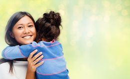 Happy mother and daughter hugging over green. Family, motherhood and people concept - happy mother and daughter hugging over green holidays lights background stock images