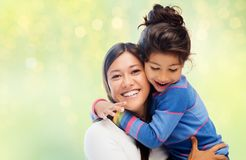 Happy mother and daughter hugging over green. Family, motherhood and people concept - happy mother and daughter hugging over green holidays lights background stock photos