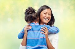 Happy mother and daughter hugging over green. Family, motherhood and people concept - happy mother and daughter hugging over green holidays lights background stock photography