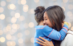 Happy mother and daughter hugging over lights Stock Images
