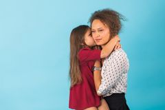 Happy mother and daughter hugging and smiling at camera isolated on blue royalty free stock image