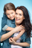 Happy mother and daughter hugging in studio on blue. Portrait of happy mother and daughter hugging in studio on blue Royalty Free Stock Photography