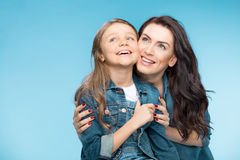 Happy mother and daughter hugging in studio on blue Stock Image