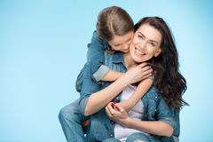 Happy mother and daughter hugging in studio on blue Royalty Free Stock Photography