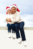 Happy mother and daughter in ice skates and christmas hats Royalty Free Stock Photography