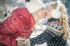 Happy mother and daughter kissing outdoor, ice skating at Christmas stock images