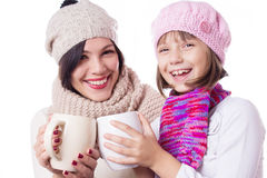 Happy mother and daughter in knitted hats with hot beverages Royalty Free Stock Images