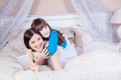 Happy mother and daughter lay in bed with digital tablet. Stock Image