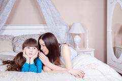 Happy mother and daughter lay in bed having fun, mother telling secret to her daughter. Stock Image